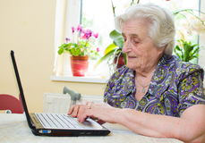 The senior hand presses the laptop keyboard. Button Stock Photo