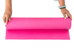 Senior hand's rolling pink yoga mat on white. Royalty Free Stock Photography