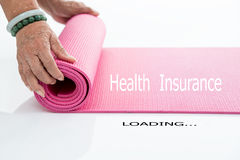 Senior hand's rolling pink yoga mat on white Stock Image