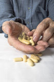 Senior hand sorting through a handful of medications Stock Photo