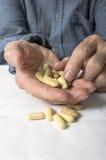 Senior hand sorting through a handful of medications Stock Photo