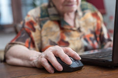 Senior hand using the mouse of a computer. Old woman hand using the mouse of a computer Royalty Free Stock Images