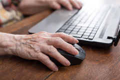 Senior hand using the mouse of a computer. Old woman hand using the mouse of a computer Stock Photo