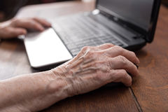 Senior hand using the mouse of a computer. Old woman hand using the mouse of a computer Stock Photography