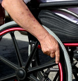 Senior hand on wheel of wheelchair. Royalty Free Stock Photo