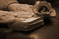 Senior hands on a bible. Senior's hands resting on a very old bible stock images