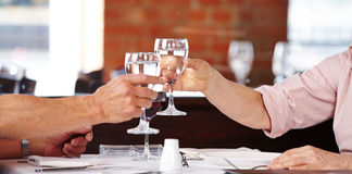 Senior hands clinking glasses. With water in a restaurant Royalty Free Stock Images