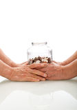 Senior hands holding a jar with coins Royalty Free Stock Photography
