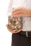 Senior hands holding jar with lots of coins Stock Photo