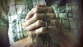 Senior hands holding rosary or crucifix while praying Stock Photos