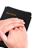 Senior Hands over Bible Stock Image