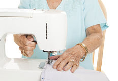 Senior hands - Sewing. Senior woman's hands using her sewing machine. White Background stock photography