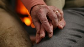 Senior hands of woman and man in front of the fireplace - comforting each other at old age stock video footage
