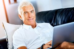 Man working on laptop at home. Senior handsome man in casual clothes working on laptop at home royalty free stock photography
