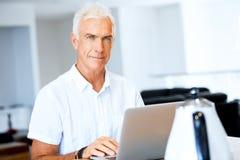 Man working on laptop at home. Senior handsome man in casual clothes working on laptop at home royalty free stock image