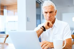 Man working on laptop at home. Senior handsome man in casual clothes working on laptop at home stock photos