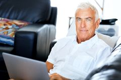 Man working on laptop at home. Senior handsome man in casual clothes working on laptop at home royalty free stock images