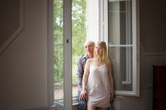 Senior Handsome Man Hugging His Young Wife Standing near the Window in Their Home During Summer Hot Day. Psychology of royalty free stock photo