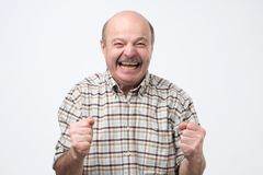 Senior handsome man laughing and looking at camera with a big grin. He is so happy to find out about his pension savings stock photos