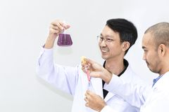 Senior handsome researcher mixing with color test tube. stock photos