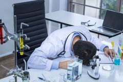Senior handsome researcher working overtime and strain stock image