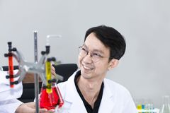 Senior handsome and smiling researcher talking with scientist stock images