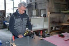 Senior handyman grinding metal in workshop. Senior handyman grinding metal in his workshop Stock Image