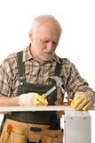 Senior handyman hammering Royalty Free Stock Image