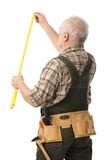 Senior handyman measuring. With tool, white background Royalty Free Stock Photography