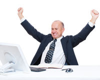 Senior happy businessman sitting in workplace. And raising hands up Stock Photo