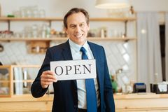 Senior happy businessman standing and holding the plate. We have opened. Senior happy confident businessman standing in his shop holding the plate and Stock Image