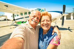 Senior happy couple taking selfie with private ultralight plane. For tour around the world - Active elderly concept with retired people enjoying pension moments Stock Photo