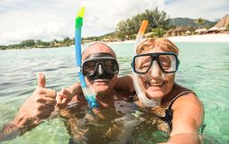 Senior happy couple taking selfie with scuba snorkeling masks. Senior happy couple taking selfie in tropical sea excursion with water camera - Boat trip stock photo