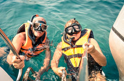 Senior happy couple using selfie stick in tropical sea excursion. Boat trip snorkeling in exotic scenarios - Concept of active elderly and fun around the Stock Image