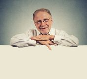 Senior happy man with blank space white banner. On gray wall background Stock Photography