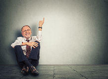 Senior happy man sitting on floor with legs crossed and pointing up Stock Images