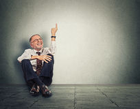 Senior happy man sitting on floor with legs crossed and pointing up. Full length studio shot isolated on gray wall background Stock Images