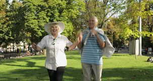 Senior happy two tourists running and bouncing in town center park. Senior happy two male and female tourists running and bouncing in town center park. Traveling stock footage