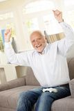 Senior happy winning computer game. Senior man happy winning computer game, raising arms, laughing, looking at camera Stock Photo