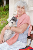 Senior happy woman hugging her white dog in the mountain Royalty Free Stock Photo