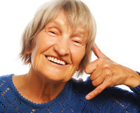 Senior happy woman is making a call me gesture Royalty Free Stock Images