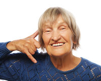 Senior happy woman is making a call me gesture Royalty Free Stock Photos