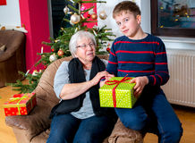 Senior has a christmas present for her grandson Stock Photos