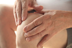 Senior has hands on his aching knee Royalty Free Stock Images