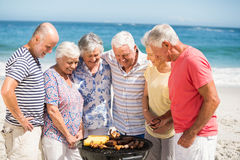 Senior having a barbecue on the beach Stock Photo