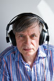 Senior with headphones. A senior male model listening to music with headphones royalty free stock images