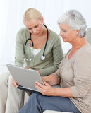 Senior with her doctor working on the laptop Stock Photography