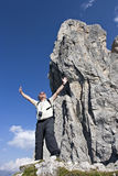 Senior hiker enjoying at summit. Active senior hiker standing in front of huge rock formation near summit lifting his arms out of joy to be in the Alps, Tyrol Royalty Free Stock Photos