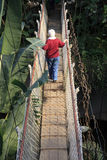 Senior hiker on a hanging bridge Stock Images