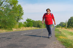 Senior hiker walking on a roadside in Ukrainian rural area at summer tim Stock Photo